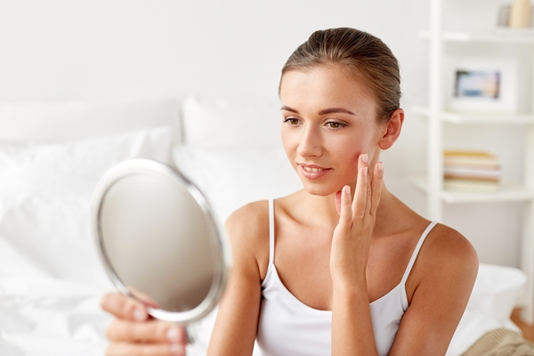 Beautiful woman with mirror sitting on bed at home bedroom and applying castor oil product on her face skin