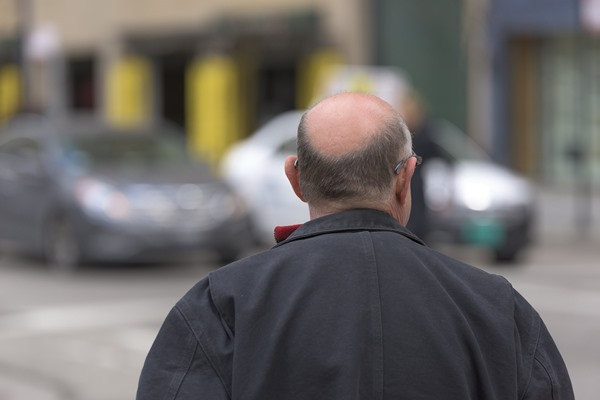Back side of an old man with bald area on top of his head
