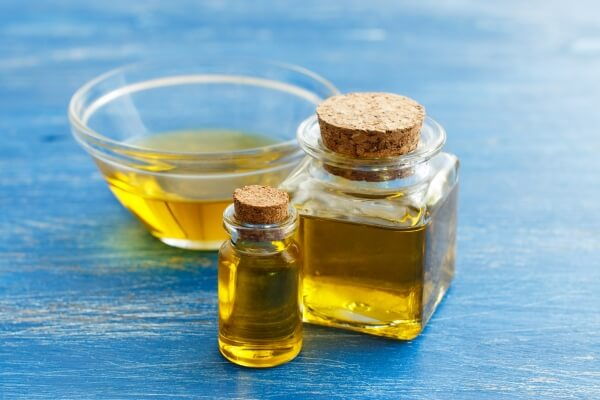Castor oil on three different glass containers: a small bottle, a decanter, and a bowl