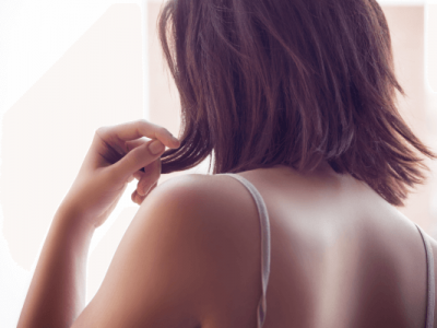 Back side of a woman with thinning hair and broken hair strands