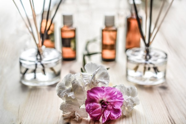 Bottles of essential oils, diffuser, and a few flowers on a wooden table