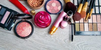 A collection of makeup products on a wooden surface