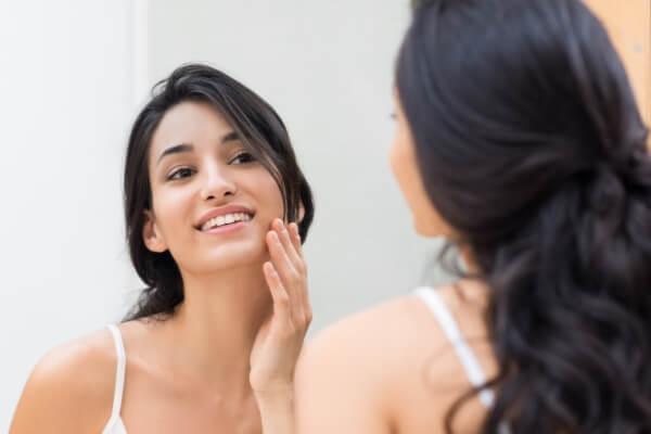 Woman applying castor oil for face
